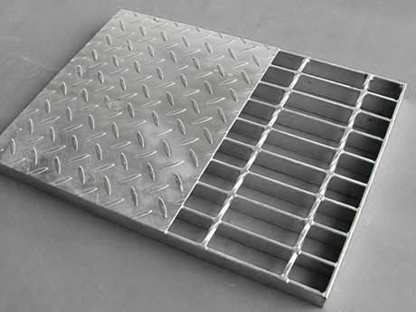 A compound steel grating with half of checkered steel plate on it.