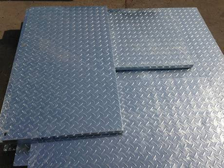 Some compound steel gratings with different sizes placed on the ground.