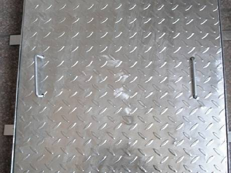 A square compound steel grating with eight bars on the four sides placed on the ground.