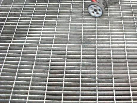 A man pushing a baby carriage through the floor made of dense steel grating.