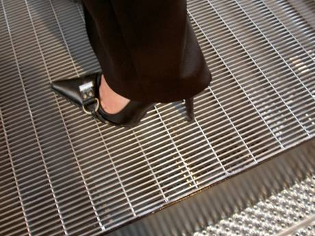 One foot wearing black high heel standing on dense steel grating without falling.