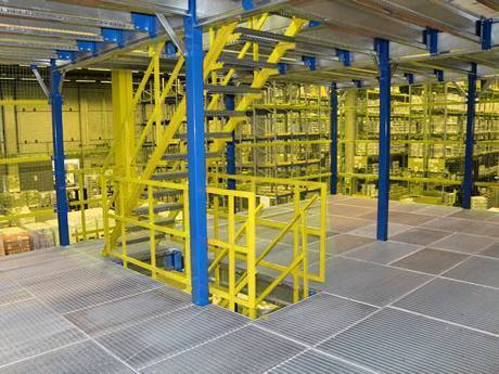 Dense steel grating used as mezzanine in a warehouse with many shelves.