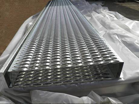 Two large diamond-strut safety grating planks placed on plastic film.