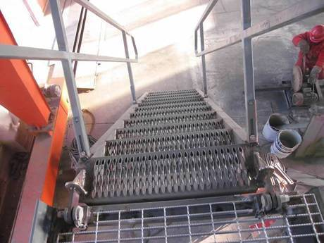 A diamond-strut safety grating is used as stair tread.