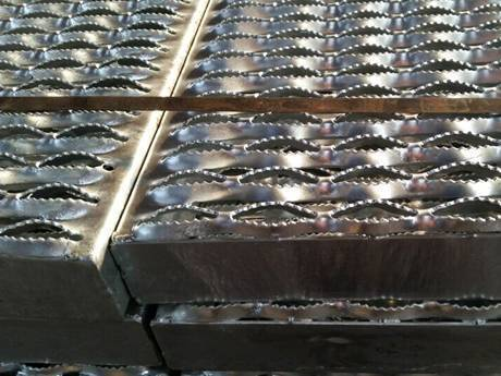 Some diamond-strut safety gratings neatly placed on the ground and fixed by the metal straps.