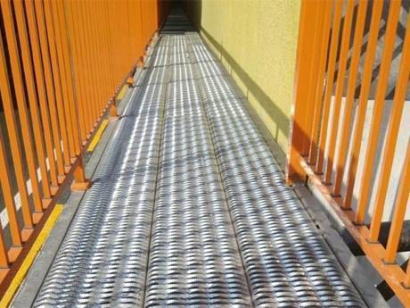 A diamond-strut safety grating is used as walkway for people to walk.
