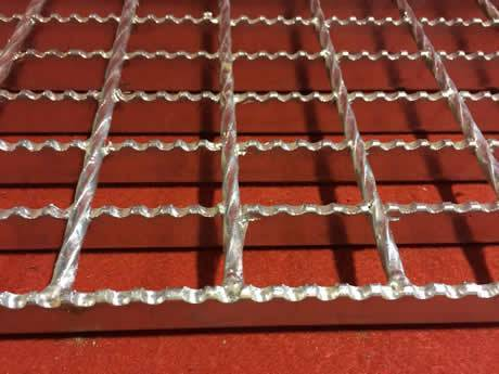 A serrated steel bar grating with hot dip galvanised surface and twisted cross bar on red background.