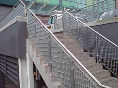 Steel grating infill panels used as stair railings outdoors.