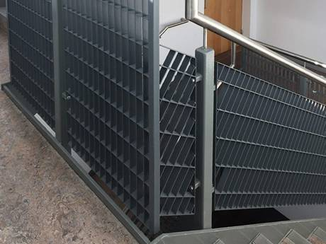 Dovetail pressure locked steel grating infill panels are installed on stair railings in the passageway.