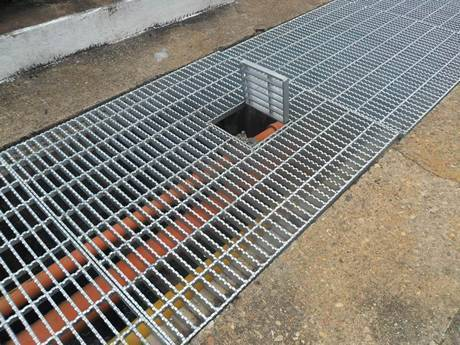 A serrated press-locked steel grating placed on the ground as trench cover.