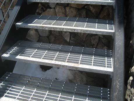 Serrated welded steel grating used as stair tread to improve safety.