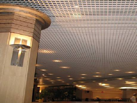 In a mall, the customers are walking and the lights shining on the steel grating ceiling.