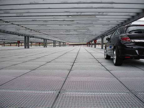 A car is passing through the steel grating floor of port parking.