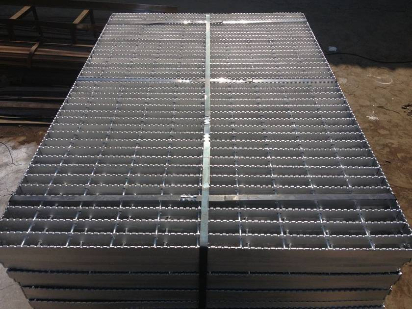 Several swage-locked steel grating piled together and fixed by the metal strap.