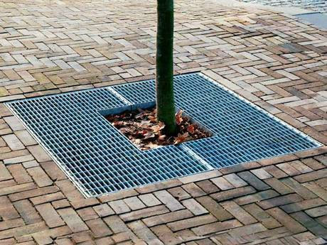 A tree cover steel grating is installed at a tree in plaza.
