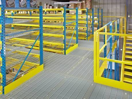 Steel grating warehouse racks with vertical blue brackets and horizontal yellow brackets.