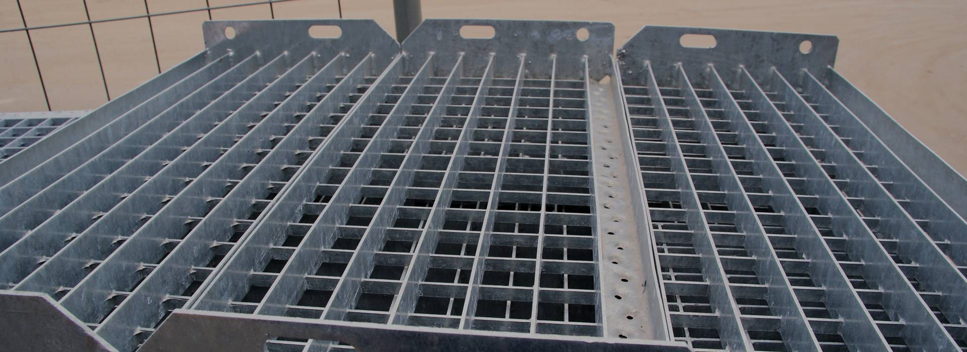 Some press-locked steel grating that the height of bearing bar and cross bar is different are on the ground.